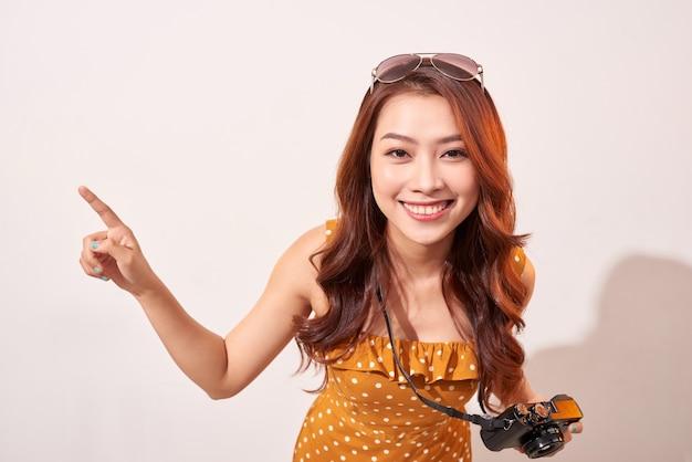 Toeristische status geïsoleerd op beige muur en vreugdevol wijzend naar de hemel. dame die camera gebruikt tijdens het reizen. onafhankelijk reizen in azië-concept.
