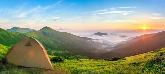 Toeristische tent gelegen in de bergen bij zonsondergang