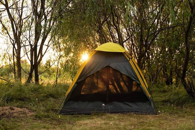 Toeristische tent in een boskamp tussen de bomen bij zonsondergang.