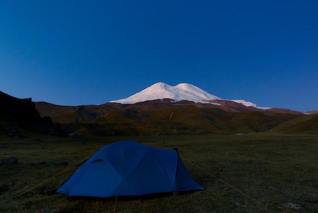 Toeristische tent op de achtergrond van de besneeuwde toppen van de elbroes in rusland