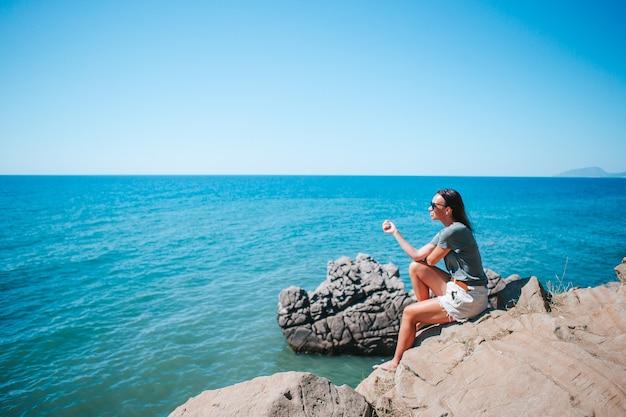 Toeristische vrouw buiten aan de rand van de klif kust