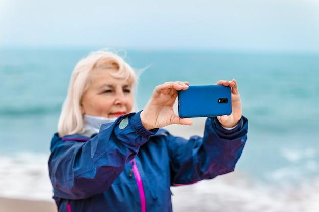 Toeristische vrouw handen met smartphone op zandstrand