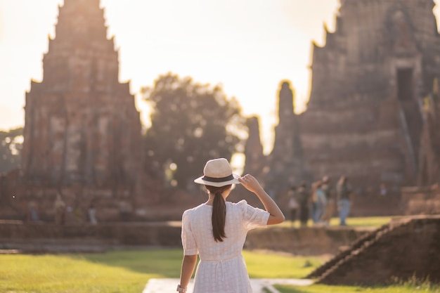 Toeristische vrouw in witte jurk een bezoek aan oude stoepa in wat chaiwatthanaram tempel in ayutthaya historical park, zomer, azië en thailand reizen concept