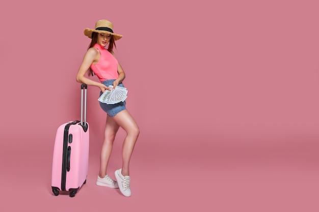 Toeristische vrouw in zomer casual kleding stro hoed met prop geld en koffer op roze achtergrond