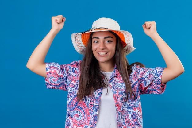Toeristische vrouw met hoed kijkt opgewonden verheugd over haar succes en overwinning haar vuisten balancerend van vreugde blij om haar doel en doelen te bereiken staande op geïsoleerd blauw