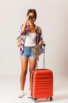 Toeristische vrouw met koffer kijkend door een verrekijker
