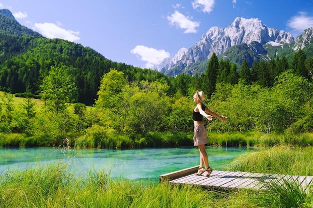 Toeristische vrouw met opgeheven armen omhoog in groene natuur achtergrond natuurreservaat in slovenië europa