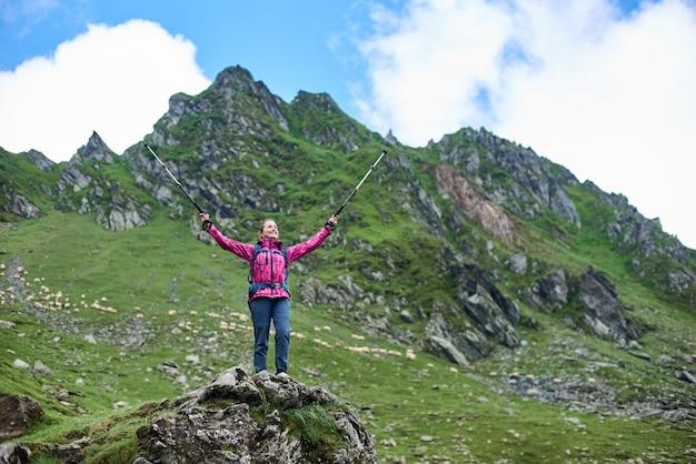 Toeristische vrouw staat met haar armen wijd open op een rots aan de voet van de berg