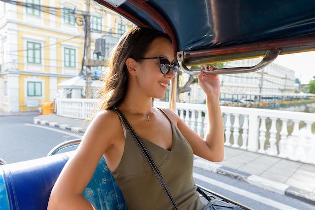 Toeristische vrouw verkennen van de stad bangkok met tuk tuk taxi