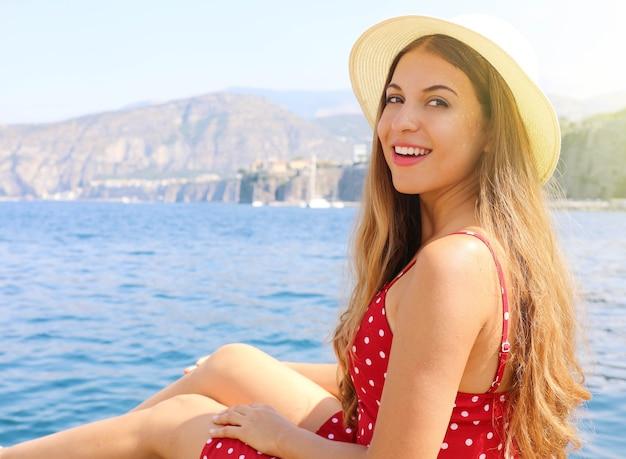 Toeristische vrouw zittend op de boot zeilen in de middellandse zee in de buurt van de stad sorrento, italië