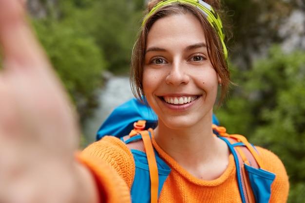 Toeristische vrouwelijke wandelaar maakt selfie portret, lacht naar de camera