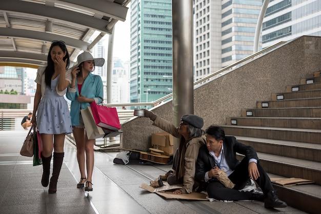 Toeristische vrouwen kijken de armen neer