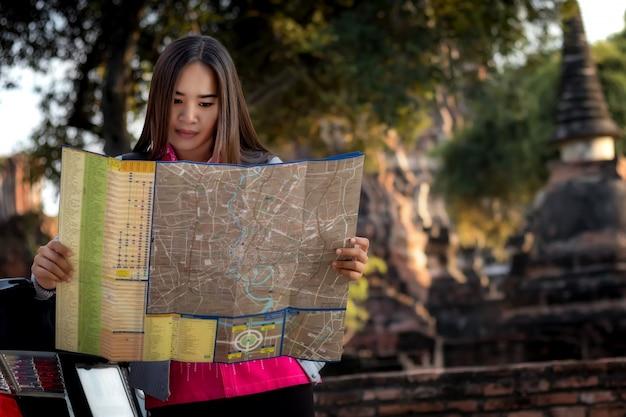 Toeristische vrouwen met het dragen van een rugzak kijken op kaart, over de tempel in ayutthaya.