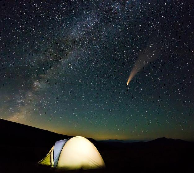 Toeristische wandelaars tent in de bergen 's nachts met sterren en neowise komeet met lichte staart in donkere nachtelijke hemel.