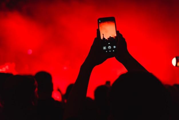 Toeschouwers tijdens een concert met smartphone