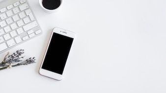 Toetsenbord dichtbij smartphone, installaties en kop van drank