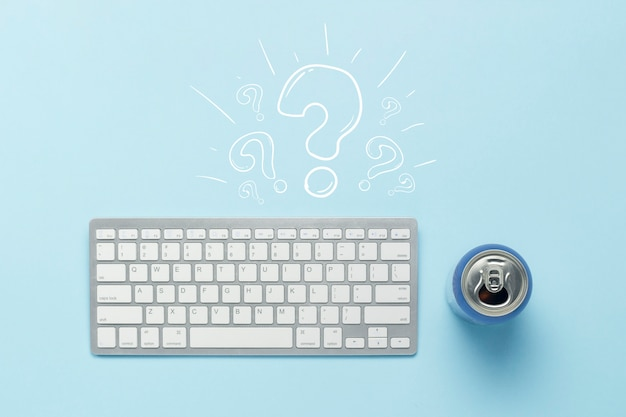 Toetsenbord en blikje met een drankje, energiedrank op een blauwe achtergrond.