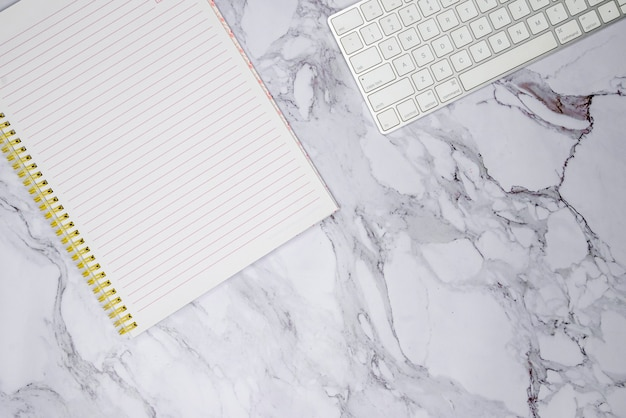 Toetsenbord en notitieboekje op marmeren oppervlak