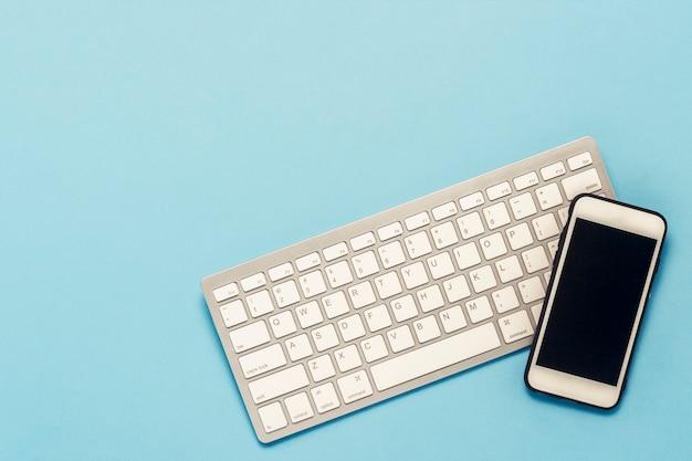 Toetsenbord en witte mobiele telefoon op een blauwe achtergrond. bedrijfsconcept, kantoorwerk, mobiele app en website. plat lag, bovenaanzicht.