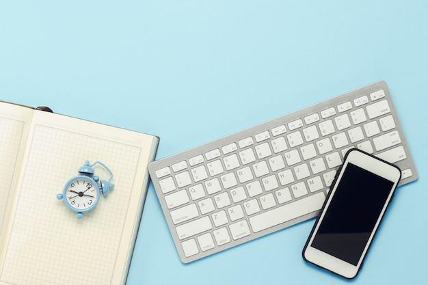 Toetsenbord en witte mobiele telefoon, wekker, dagboek op een blauwe achtergrond. bedrijfsconcept, kantoorwerk, mobiele app en website. plat lag, bovenaanzicht.