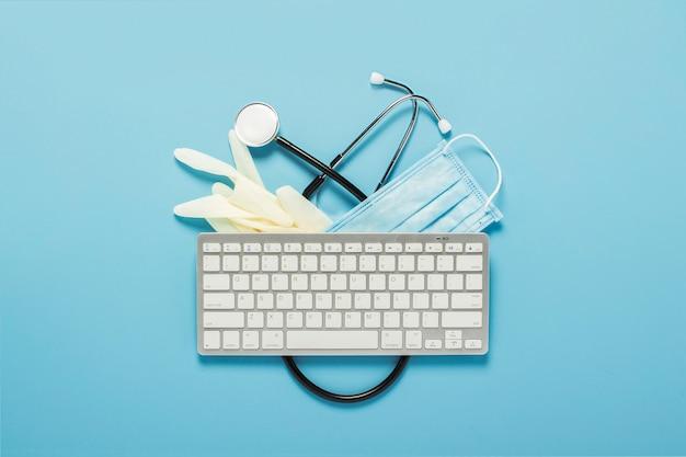 Toetsenbord, medische stethoscoop, latex handschoenen en een beschermend masker op een blauwe achtergrond. concept geneeskunde, ziekenhuis, veiligheid, epidemie, dokter, online, consultatie.