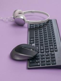 Toetsenbord met een draadloze muis en witte koptelefoon op een paarse ondergrond