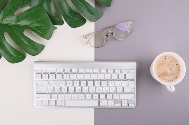 Toetsenbord met koffiekop en glazen