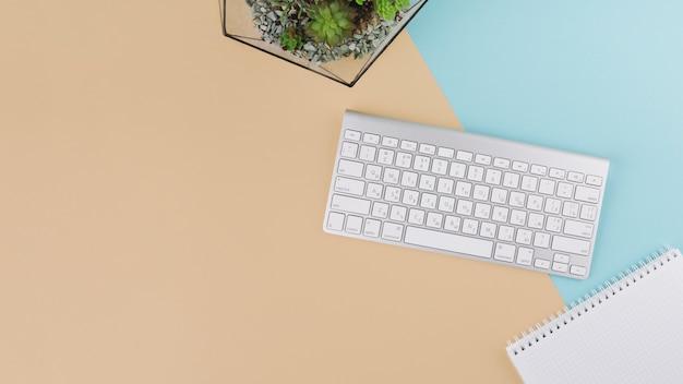 Toetsenbord met notitieboekje en plant
