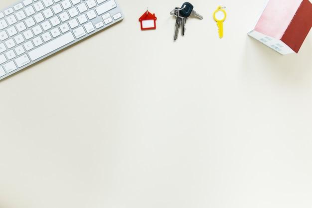 Toetsenbord met sleutels en huismodel op witte achtergrond