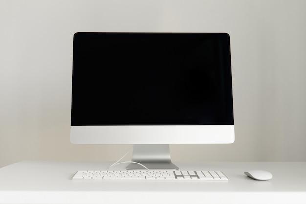 Toetsenbord, muis, computerscherm met zwart leeg scherm. vooraanzicht. ontwerperwerkruimte op grijze achtergrond. minimalistisch thuiskantoor.