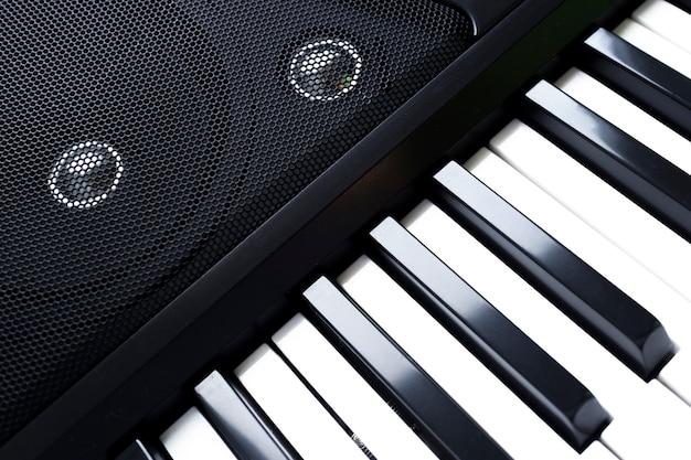 Toetsenbord van piano of elektronische digitale synthesizer met luidsprekers.