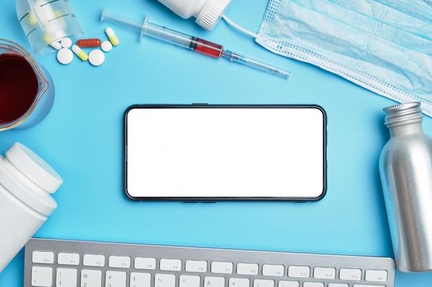 Toetsenbord, witte blikjes, spuit, beschermend masker op een blauwe achtergrond. smartphone met plaats voor bovenaanzicht.