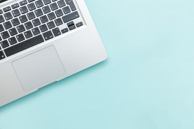 Toetsenbordlaptop computer op blauw pastelkleurbureau dat wordt geïsoleerd