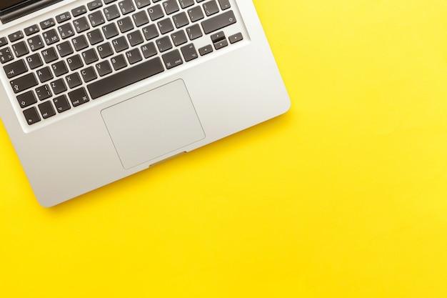 Toetsenbordlaptop computer op geel bureau wordt geïsoleerd dat