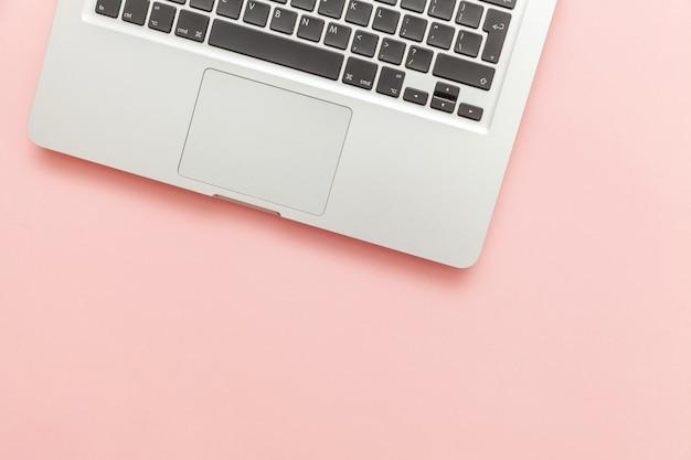 Toetsenbordlaptop computer op roze pastelkleurbureau dat wordt geïsoleerd