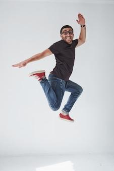 Toevallig gekleed beeld van het vrolijke jonge mens springend over wit