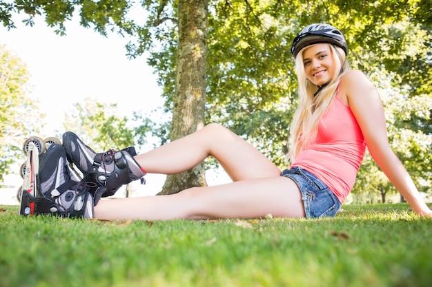 Toevallig glimlachend blonde die rolbladen en helm dragen