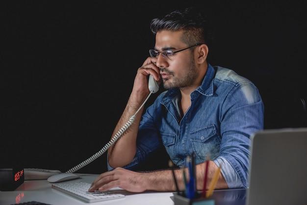 Toevallige aziatische zakenman die telefoongesprek bij nacht in het bureau beantwoordt