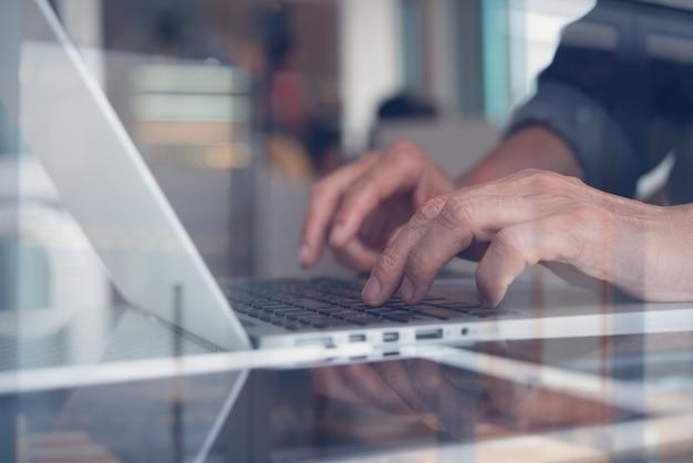 Toevallige bedrijfsmens die met laptop werkt