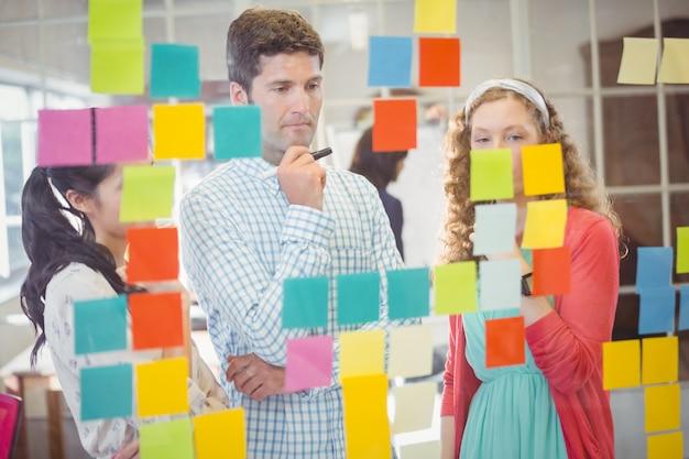 Toevallige collega's die kleverige nota's over muur bekijken
