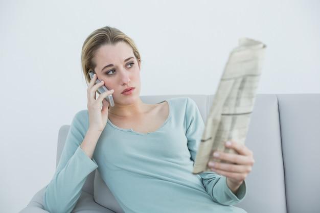 Toevallige denkende vrouw die terwijl het zitten op laag telefoneert