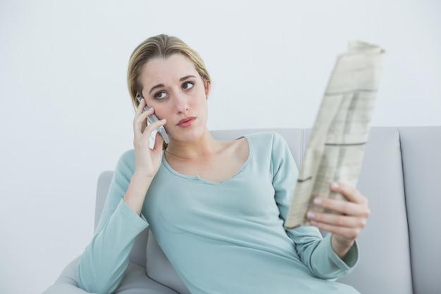 Toevallige ernstige vrouw die zitting op laag telefoneert