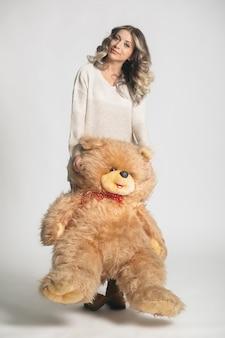 Toevallige glimlachende jonge vrouw die in gebreide kleren grote zachte teddybeer houden