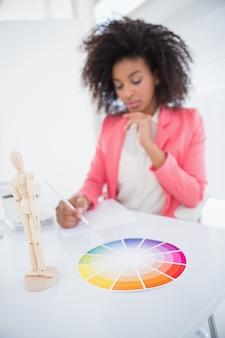Toevallige grafische ontwerper die bij haar bureau het schetsen werkt