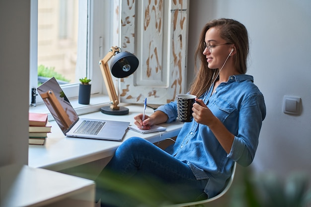 Toevallige jonge glimlachende slimme studente in hoofdtelefoons tevreden met het leren van vreemde taal. vrouw maakt aantekeningen op notitieblok tijdens het bekijken van webinar videocursussen. online onderwijs