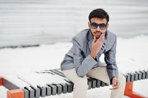 Toevallige jonge indische mens in zilveren jasje en zonnebril die bij de winterdag wordt gesteld en op bank zit.