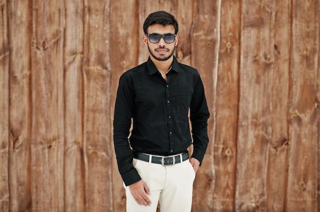Toevallige jonge indische mens in zwart die overhemd en zonnebril tegen houten achtergrond wordt gesteld.