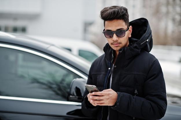 Toevallige jonge indische mens in zwart jasje en zonnebril die tegen suvauto wordt gesteld met telefoon bij handen.
