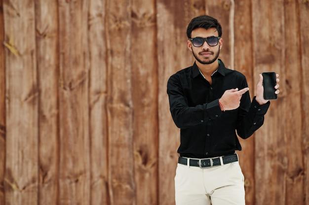 Toevallige jonge indische mens in zwart overhemd en zonnebril die tegen houten achtergrond wordt gesteld die bij mobiele telefoon tonen.