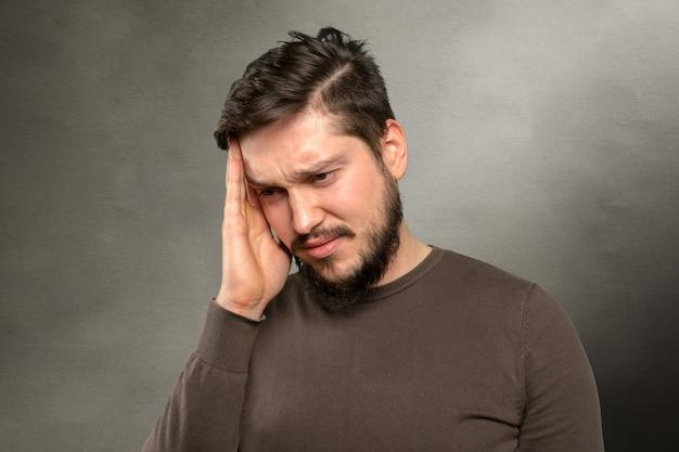Toevallige kaukasische jonge mens die aan hoofdpijn lijdt